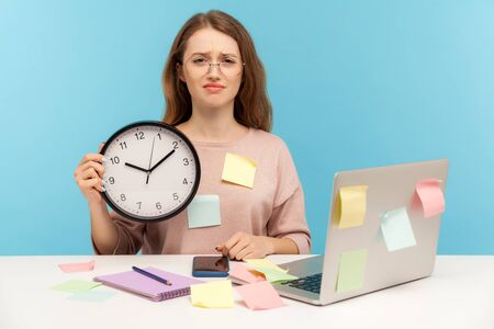 Overtime work. Exhausted fatigued upset woman employee in eyeglasses sitting at workplace office, all covered with sticky notes and holding big clock. indoor studio shot isolated on blue background Imagens