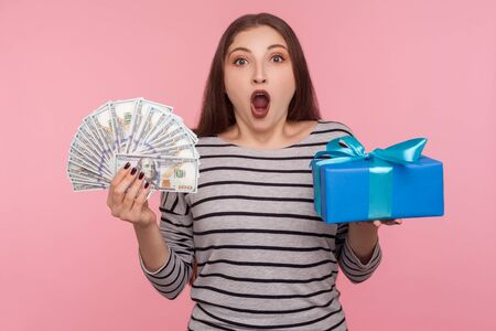 Wow, unbelievable bank loan for holiday shopping! Portrait of surprised woman in striped sweatshirt holding dollar bills and gift box, looking at camera with shocked expression. studio shot isolated