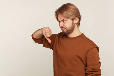 I don't like this! Portrait of displeased bearded man in sweatshirt showing thumbs down and looking dissatisfied disappointed, disagree with suggestion. indoor studio shot isolated on gray background Banco de Imagens