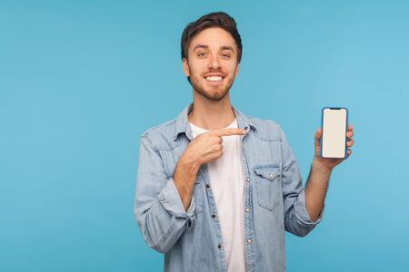Portrait of cheerful happy man in worker denim shirt smiling and showing mobile device, cell phone with mock up empty display to advertise. indoor studio shot isolated on blue background, copy space Foto de archivo