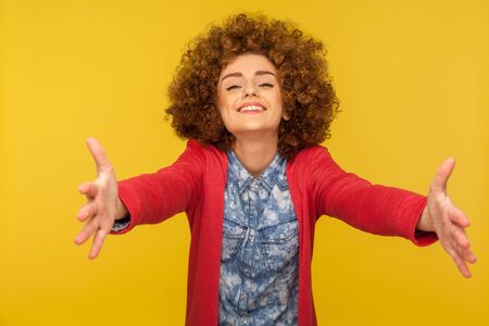 Who wants free hugs? Portrait of friendly curly-haired woman welcoming with wide raised hands and ready to embrace, sharing love, sincere meeting guests with smile. indoor studio shot, isolated