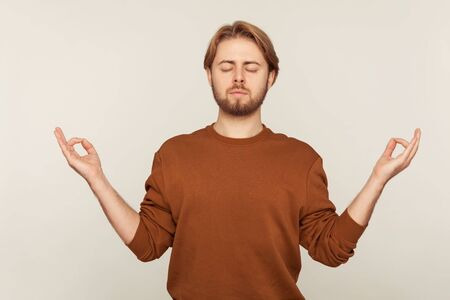 Balanced mind, relaxation. Portrait of peaceful man with beard in sweatshirt standing calm down with namaste gesture and meditating, practicing yoga. indoor studio shot isolated on gray background