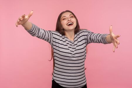 Come into my arms! Portrait of hospitable excited friendly woman in striped sweatshirt raising hands to embrace, welcoming guests with charming pleased smile. studio shot isolated on pink background Stock fotó