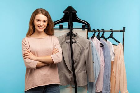 Confident happy woman, professional expert fashion stylist standing near clothes hang on shelf in designer store, selling trendy outfit in shop boutique. indoor studio shot isolated on blue background