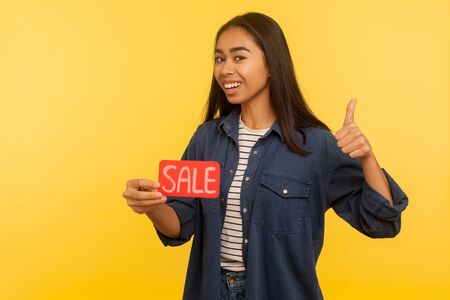 I like thrift shopping! Satisfied cheerful girl in stylish denim shirt holding Sale inscription and showing thumbs up, like gesture, enjoying discounts, Black Friday. indoor studio shot, isolated Stok Fotoğraf