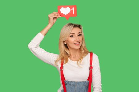 Follow and like social media blog. Portrait of lovely smiling adult woman in stylish denim overalls holding network heart icon over head, emoji notification button. indoor studio shot, isolated