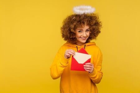 Love message. Portrait of happy curly-haired angelic woman with saint nimbus holding letter in envelope and looking at camera with playful smile. indoor studio shot isolated on yellow background Archivio Fotografico