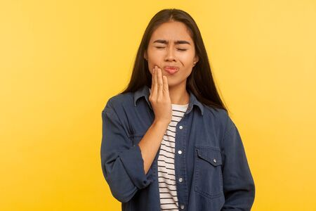 Toothache. Portrait of girl in denim shirt touching sore cheek, frowning from acute pain, suffering cracked teeth, gum recession, dental problems. indoor studio shot isolated on yellow background