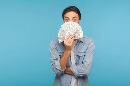 Portrait of funny amazed man in worker denim shirt peeking out of dollar banknotes with surprised expression, big eyes in amazement, shocked by money profit, lottery win. indoor studio shot isolated