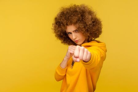 Struggle and fighting spirit. Portrait of aggressive curly-haired woman in urban style hoodie attacking with clenched fists, threatening to punch. indoor studio shot isolated on yellow background Фото со стока