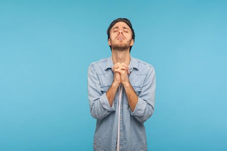 Please, I'm begging! Portrait of frustrated man in denim shirt keeping hands in prayer gesture, appealing to god with imploring expression, sincere asking help. indoor studio shot, blue background