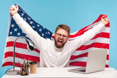 Extremely happy businessman raising American flag, yelling crazy joy in office workplace, celebrating labor day or US Independence day 4th of july, government employment support. indoor, isolated