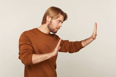 I refuse! Side view of man with beard in sweatshirt showing definitive no, confident stop gesture and looking with negative expression, warning and declining conflict. indoor studio shot isolated