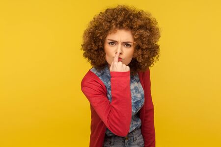 This is lie! Portrait of angry woman with fluffy curly hair touching nose, showing liar gesture, expressing distrust of false suggestion, deception. indoor studio shot isolated on yellow background Stockfoto