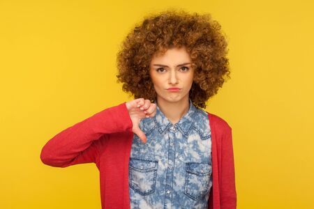 I don't like this! Portrait of upset woman with curly hair in casual outfit standing with thumbs down gesture, expressing disapproval, criticizing bad service. indoor studio shot, yellow background Banco de Imagens