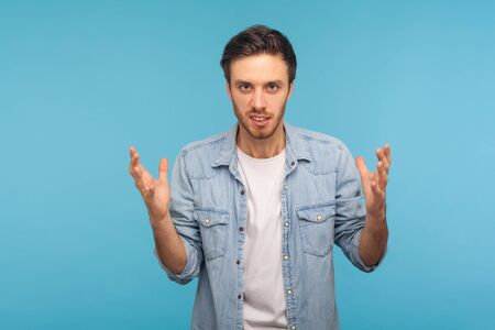 Aggression and conflict. Portrait of irritated man in worker denim shirt raising hands and clenching teeth with anger, hate emotions, annoyed by problem. indoor studio shot isolated on blue background
