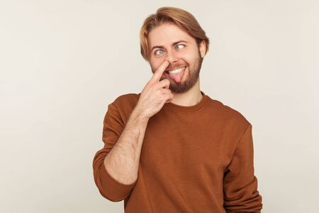 Portrait of dumb brainless comical man with beard in sweatshirt picking nose, looking cross eyed with humorous stupid expression, drilling booger mucus. indoor studio shot isolated on gray background