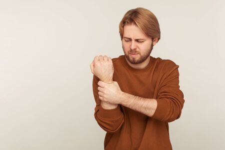 Sprain wrist. Portrait of bearded man in sweatshirt massaging sore arm, feeling numb stiff muscles, symptom of carpal tunnel syndrome, joint inflammation. studio shot isolated on gray background Stock Photo