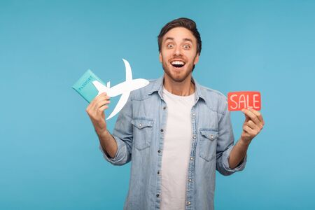 Portrait of amazed happy tourist man in denim shirt holding paper plane, passport and Sale word, planning vacation abroad with low cost air transportation. studio shot isolated on blue background