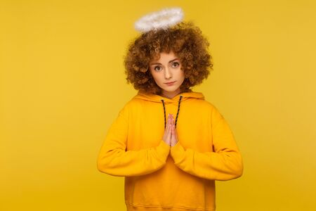 Portrait of unhappy curly-haired hipster woman with saint nimbus holding hands in prayer and looking with obedient imploring expression, asking help. indoor studio shot isolated on yellow background Archivio Fotografico