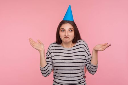 I don't know, sorry! Portrait of confused clueless woman with party cone hat shrugging shoulders, looking embarrassed, not sure and doubting about right choice. studio shot isolated on pink background