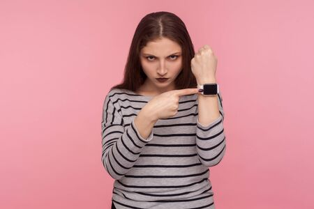 Hurry up! Portrait of angry woman in striped sweatshirt nervous about late hour, pointing wrist watch with display mock up, looking anxious, worried about deadline. indoor studio shot, pink background