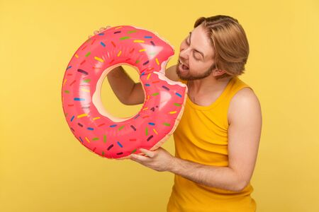Crazy happy guy in undershirt biting funny pink rubber ring, pretending to eat inflatable donut, having fun, excited by vacation seaside, relax on tropical resort. indoor studio shot yellow background