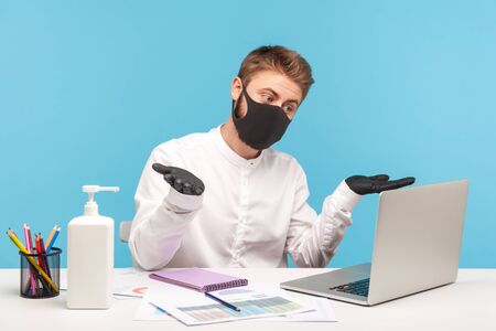 Confused man office employee talking on video call, shrugging shoulders looking uncertain at laptop screen, wearing mask, hygienic gloves to prevent coronavirus at workplace. studio shot isolated