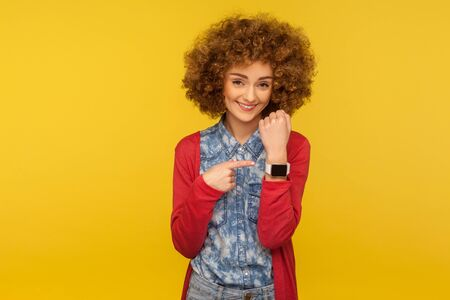 Portrait of positive cheerful woman with curly hair showing wrist watch and looking happily at camera, reminding of late time, asking to hurry. indoor studio shot isolated on yellow background Archivio Fotografico