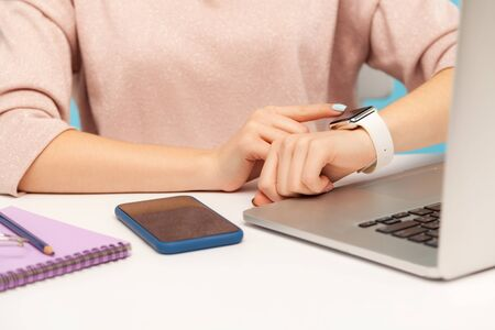 Closeup of female employee looking at smart watch on her hand while working on laptop in office, checking hour to take break, touching screen to turn off alarm clock. indoor studio shot, isolated Archivio Fotografico