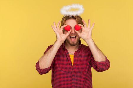Funny bearded guy saint halo covering eyes with toy hearts as if looking with love, expressing romantic feelings, affection adoration in relations. indoor studio shot isolated on yellow background