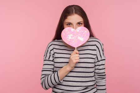 Be my Valentine! Portrait of coquettish cheerful woman peeping out shiny pink heart with playful happy look, demonstrating love care, romantic feelings. indoor studio shot isolated on pink background 版權商用圖片