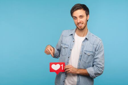 Click Like and subscribe! Portrait of handsome blogger man in denim shirt pointing at social media heart button, emoji counter, follower notification. indoor studio shot isolated on blue background