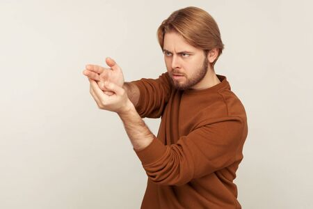 Aimed shot. Portrait of concentrated focused bearded man pointing finger gun gesture to target, threatening to kill, shooting with hand pistol and looking menace. indoor, isolated on gray background