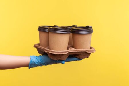 Profile side view closeup of human hand in blue surgical gloves holding and showing cups of hot takeaway mug drink in hand. indoor, studio shot, isolated on yellow background.