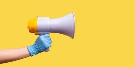 Profile side view closeup of human hand in blue surgical gloves holding megaphone. indoor, studio shot, isolated on yellow background.
