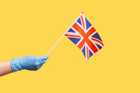 Profile side view closeup of human hand in blue surgical gloves holding flag of a constituent unit of the United Kingdom. June 4: British Independence Day. indoor shot, isolated on yellow background.