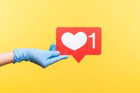Profile side view closeup of human hand in blue surgical gloves holding social media like stick. indoor, studio shot, isolated on yellow background.