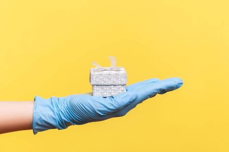 Profile side view closeup of human hand in blue surgical gloves holding small gift box. sharing, giving wedding proposal, or delivery concept. indoor, studio shot, isolated on yellow background. Banque d'images
