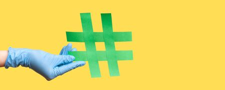 Profile side view closeup of human hand in blue surgical gloves holding green hashtag. indoor, studio shot, isolated on yellow background.