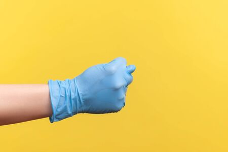 Profile side view closeup of human hand in blue surgical gloves showing gesture. indoor, studio shot, isolated on yellow background.