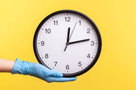Profile side view closeup of human hand in blue surgical gloves holding analog clock. indoor, studio shot, isolated on yellow background.