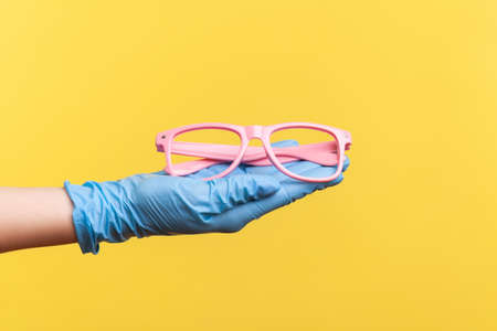 Profile side view closeup of human hand in blue surgical gloves holding and giving pink eyeglasses frame. indoor, studio shot, isolated on yellow background.