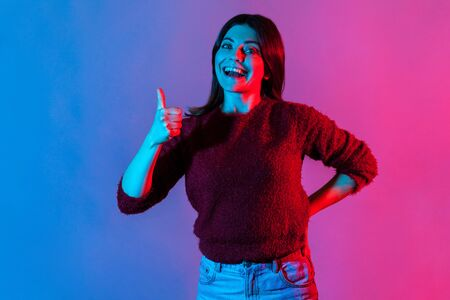 Well done, good job! Neon light portrait of joyful brunette woman showing thumbs up, like gesture to camera and smiling broadly, expressing approval, excellent feedback. indoor studio shot isolated