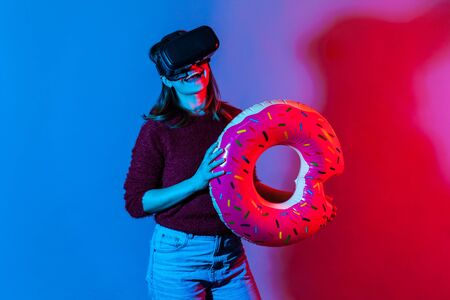 Happy smiling tourist girl in VR glasses holding rubber ring, watching virtual travel tours to seaside, journey in augmented reality, dreaming of vacation in tropical country. neon light studio shot