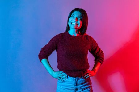 Happy emotions. Neon light portrait of joyful delighted woman in pullover looking up with wide toothy smile, cheerful grinning, laughing after hearing funny joke, anecdote. indoor studio shot isolated