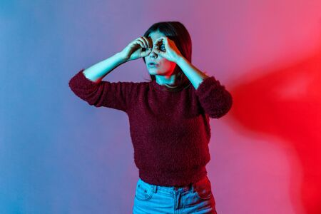 Neon light portrait of woman looking through binoculars hand gesture with attentive view, observing far distance and zooming to discover something interesting, spying. indoor studio shot isolated