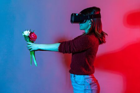 Side view, cheerful girl in VR glasses headset holding flowers bouquet, giving tulips to virtual friend and smiling, enjoying spring in cyberspace augmented reality. colorful neon light studio shot Foto de archivo - 150552770