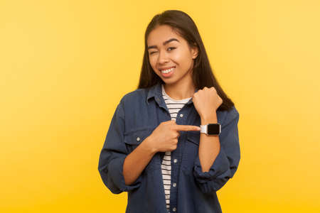 Remember the hour! Portrait of cheerful girl in denim shirt pointing wristwatch and winking playfully, showing agreed meeting time, happy minutes. indoor studio shot isolated on yellow background