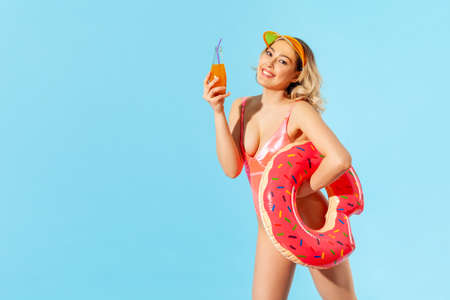 Portrait of cheerful glamour sexy woman in swimsuit and sun hat holding rubber ring, fresh juice and looking at camera with toothy smile, enjoying rest on vacation resort. indoor studio shot isolated 免版税图像